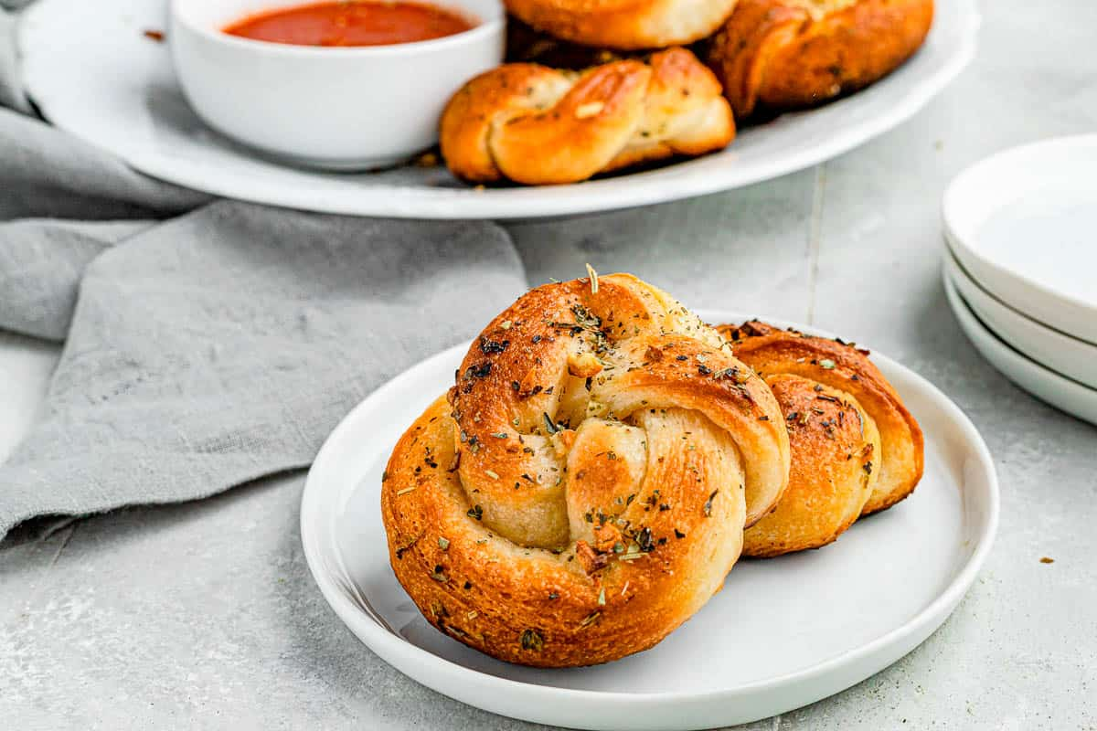 A wide shot of garlic knots piled onto a plate with marinara dipping sauce on the side.