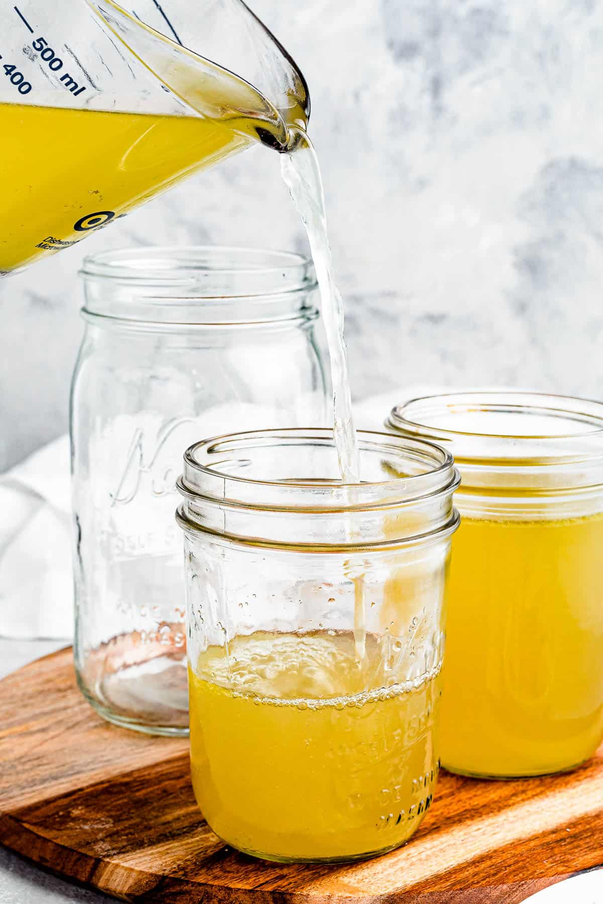 Chicken broth being poured from a large measuring cup into several jars.