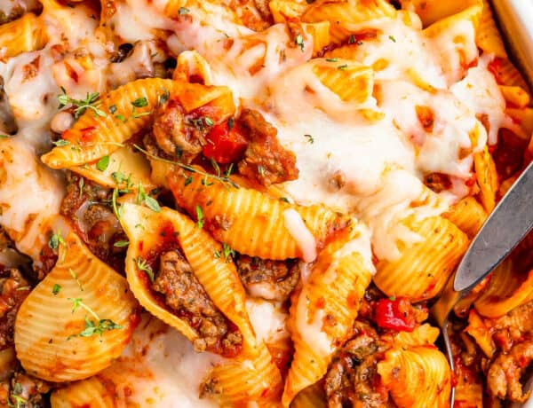 A serving dish filled with cooked pasta shells and ground beef in tomato sauce, topped with melted mozzarella.