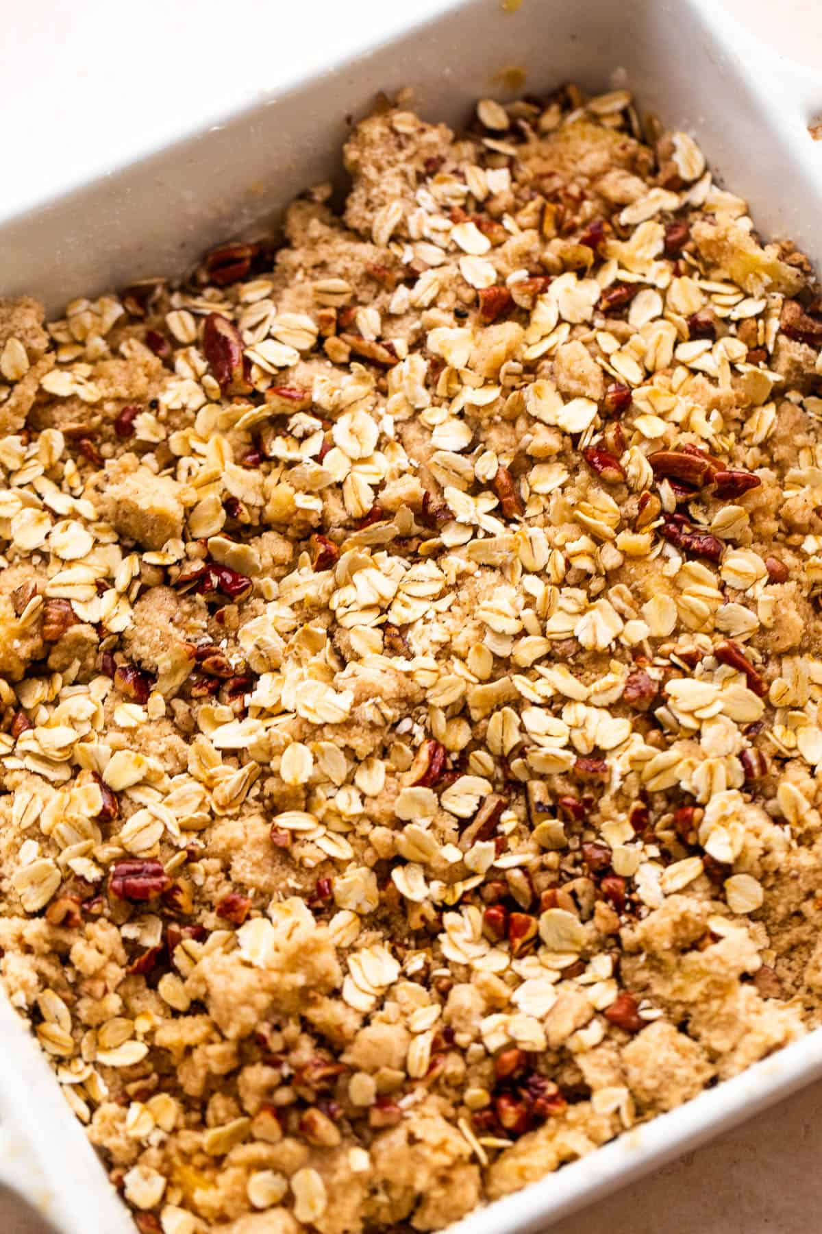 squared baking dish with peach slices covered in oats, flour, and pecans