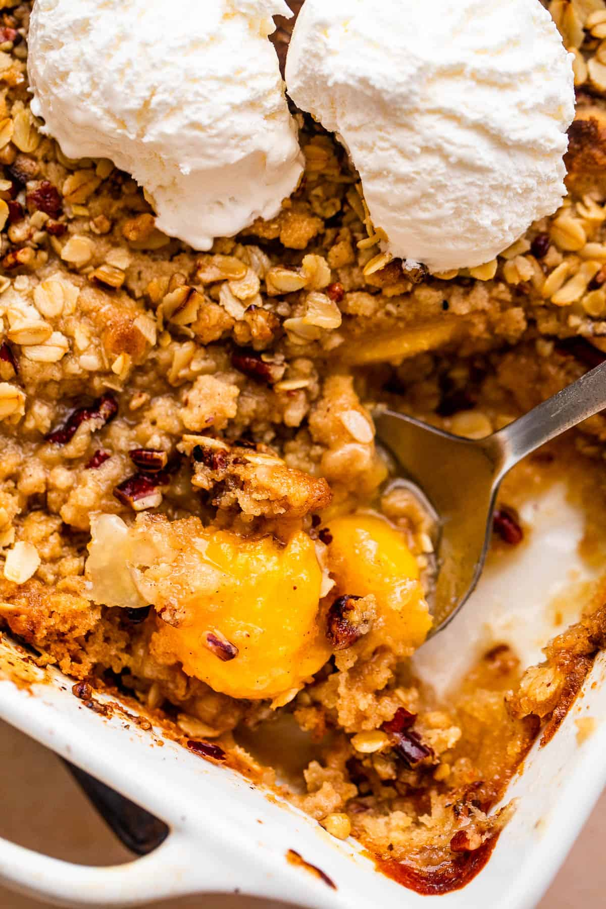 peach crisp in a white baking dish topped with scoops of vanilla ice cream