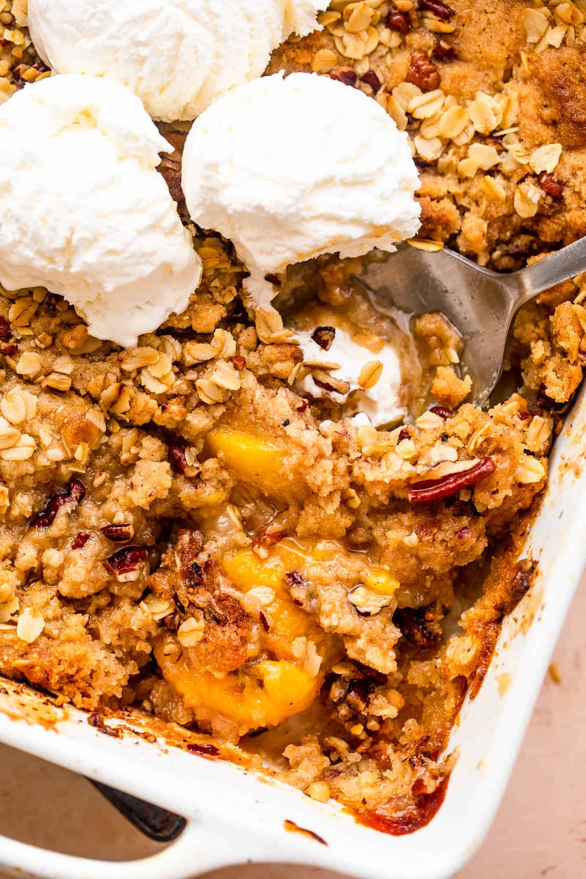 peach crisp in a white baking dish topped with three scoops of vanilla ice cream