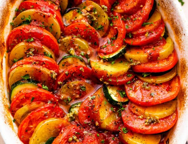 overhead shot of zucchini, tomato, and potato slices arranged accordion style in a baking dish.