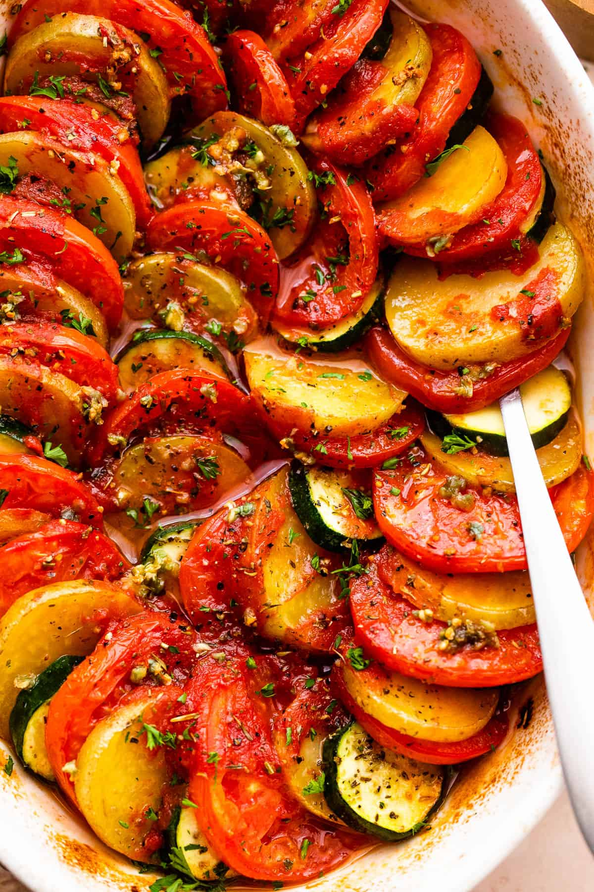 close up shot of zucchini slices, tomato slices, and potato slices arranged accordion style in a baking dish.