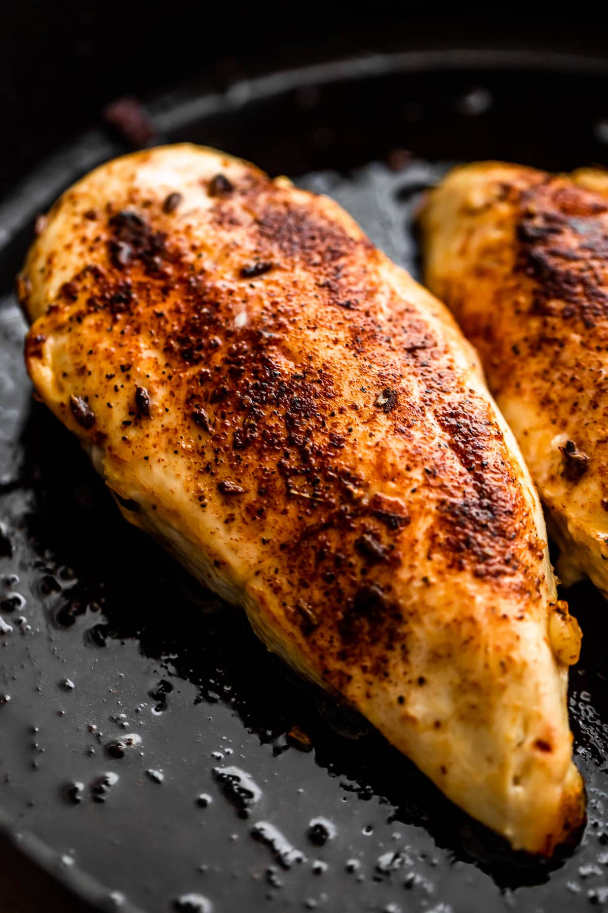 cooking chicken breasts in a cast iron skillet.