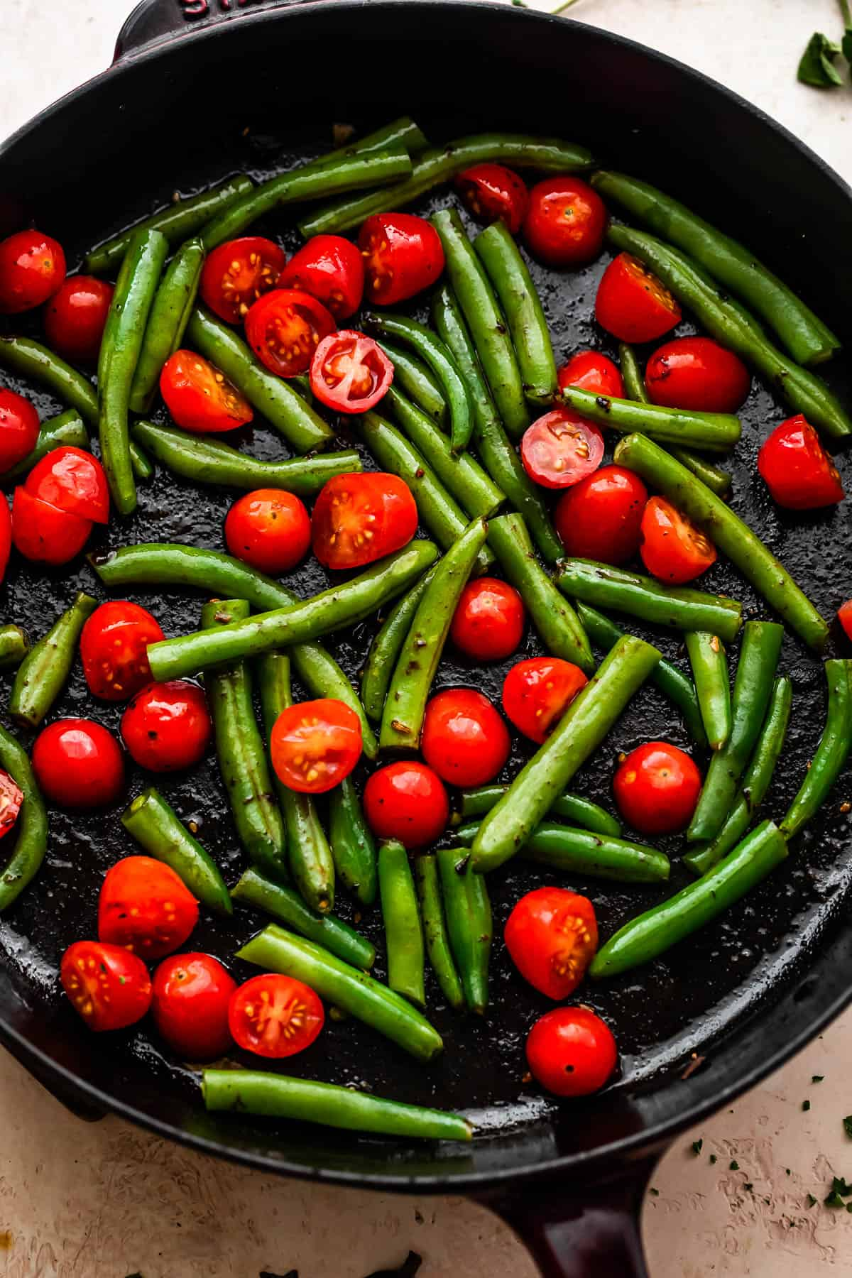 overhead shot of pan frying cherry tomatoes and green beans in a cast iron skillet