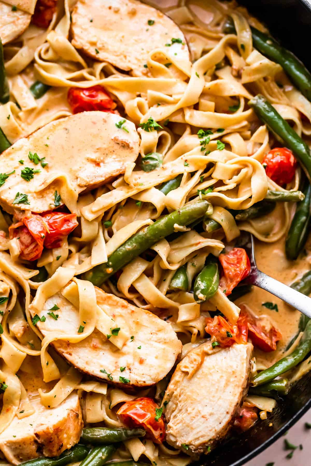 fettuccine pasta in creamy sauce with slices of blackened chicken, tomatoes, and green beans