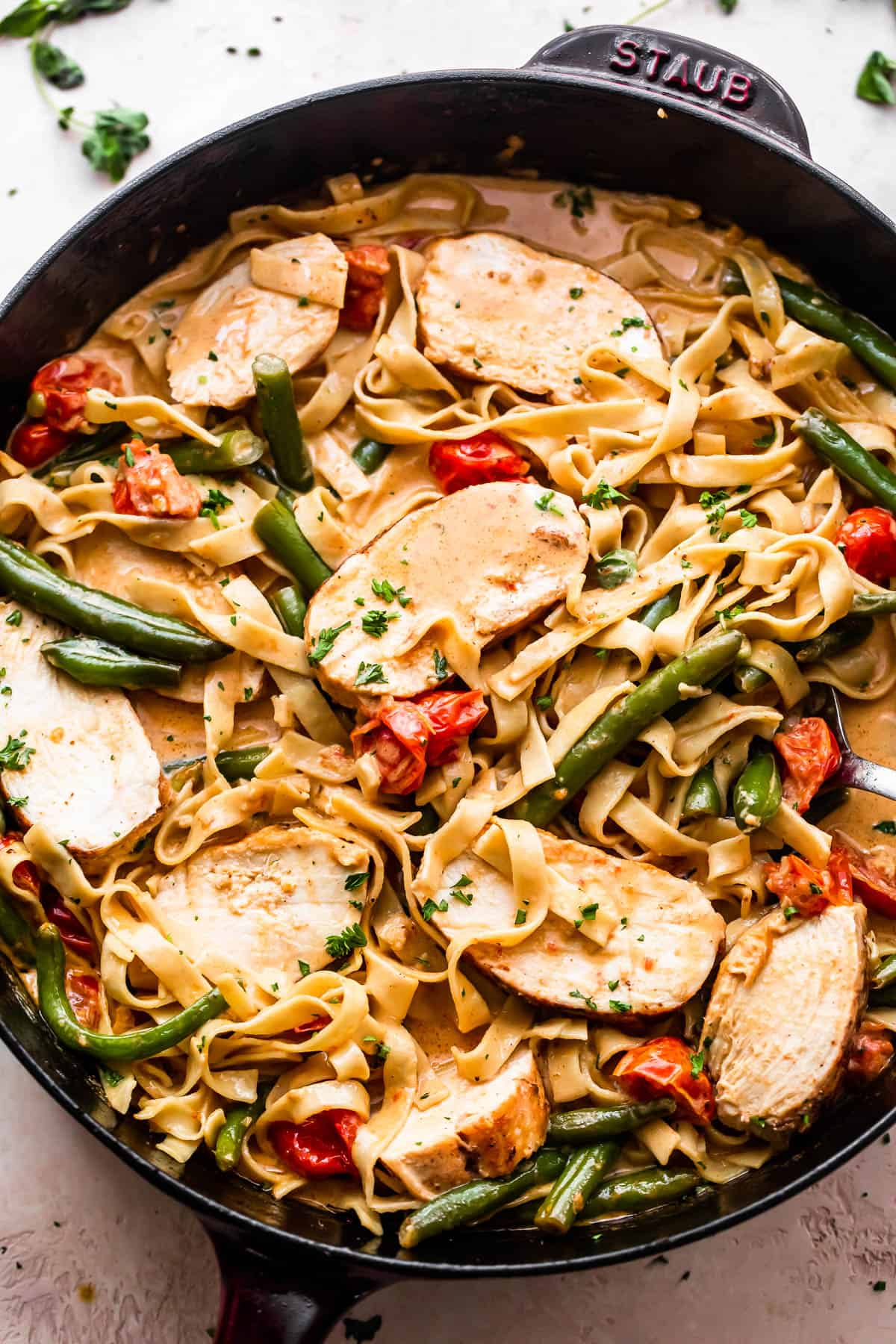 overhead shot of a skillet with Creole Blackened Chicken with Pasta, tomatoes, and green beans