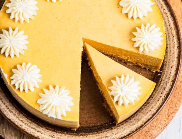 Pumpkin cheesecake decorated with whipped cream.