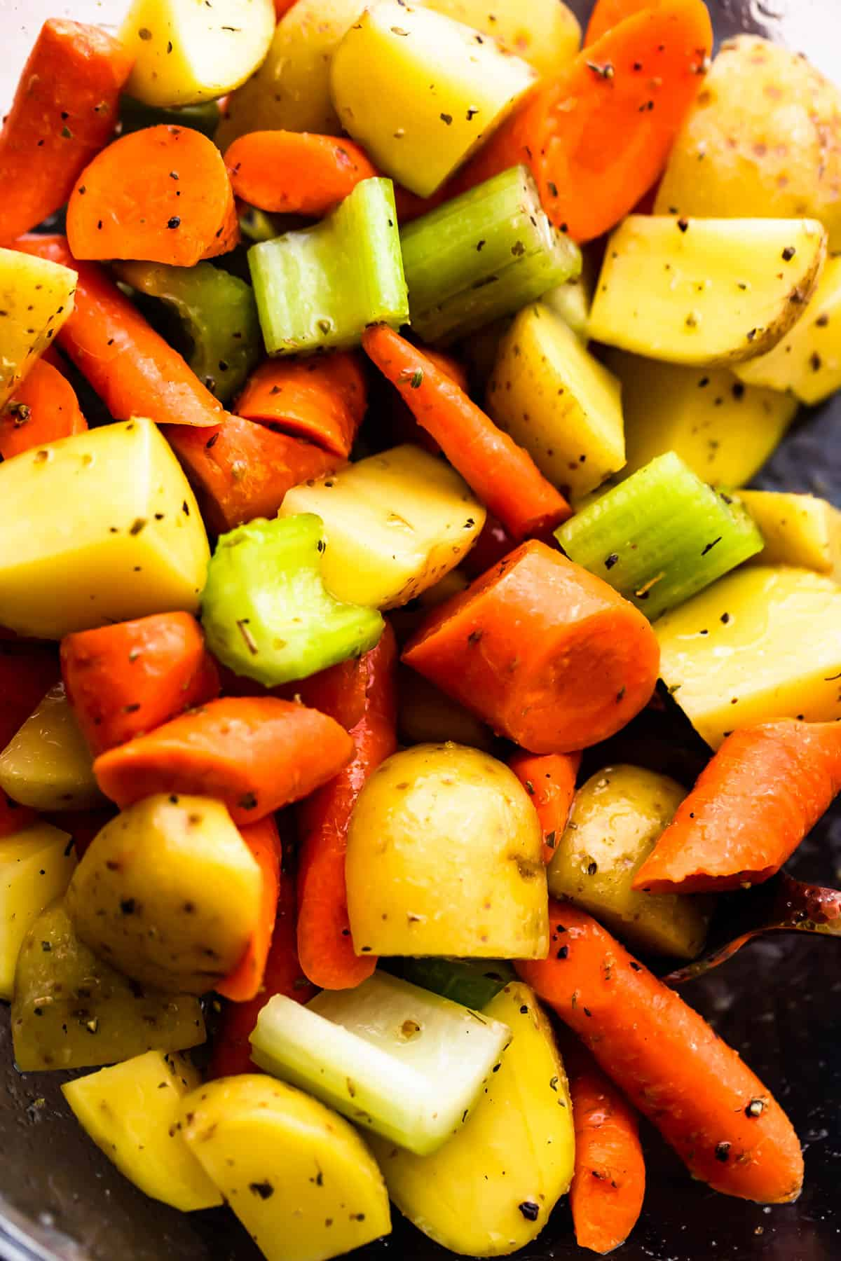 glass bowl with chopped pieces of carrots, celery, and potatoes
