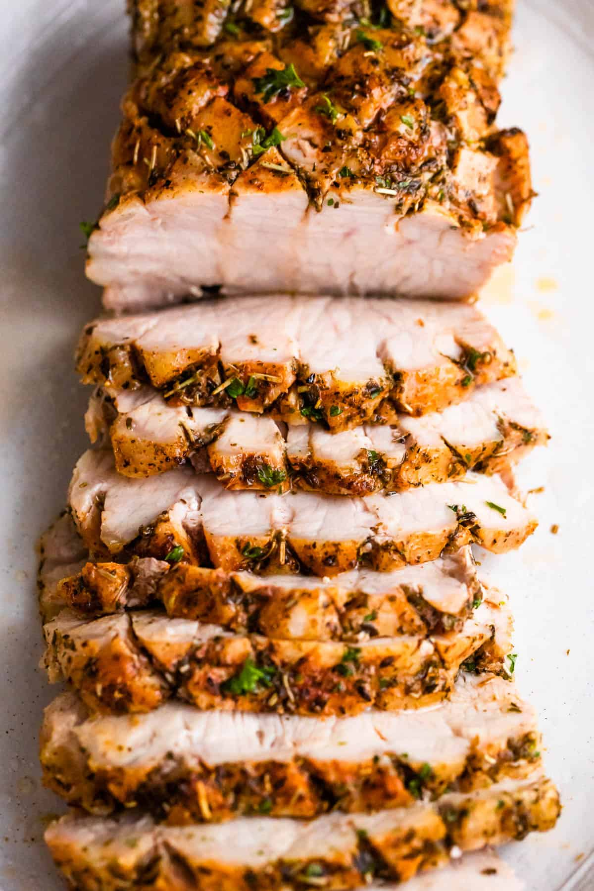overhead shot of cooked and sliced pork roast set on a white background