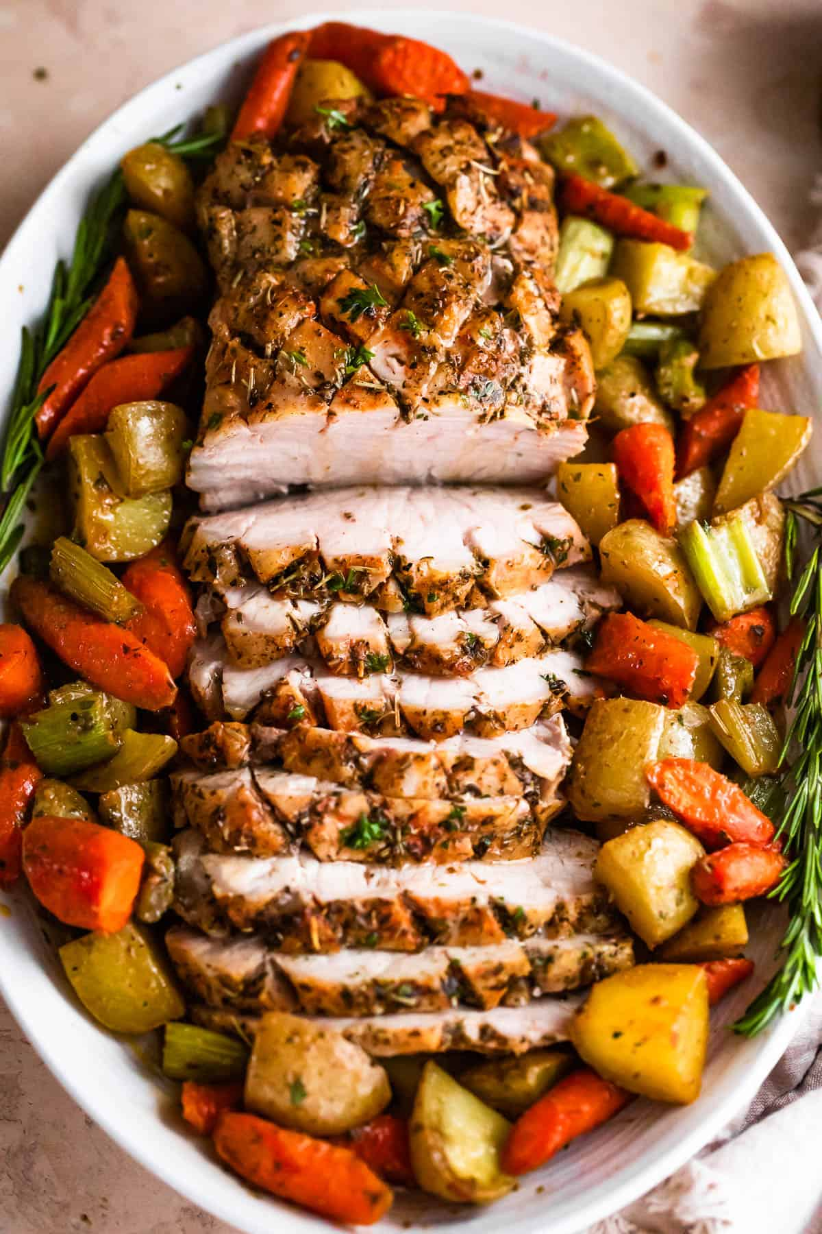 overhead shot of oval plate with cooked and sliced pork loin roast and roasted vegetables arranged around the roast