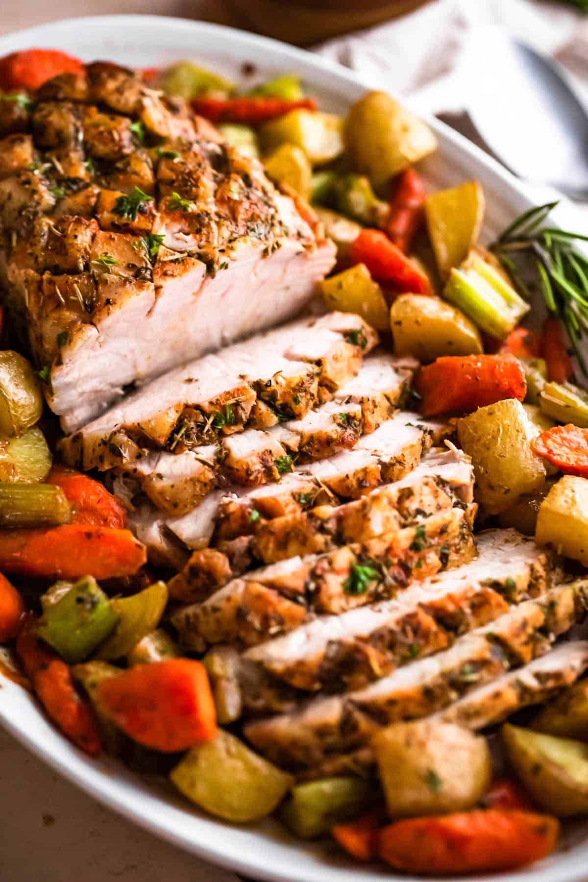 side shot of oval plate with cooked and sliced pork loin roast and roasted vegetables arranged around the roast