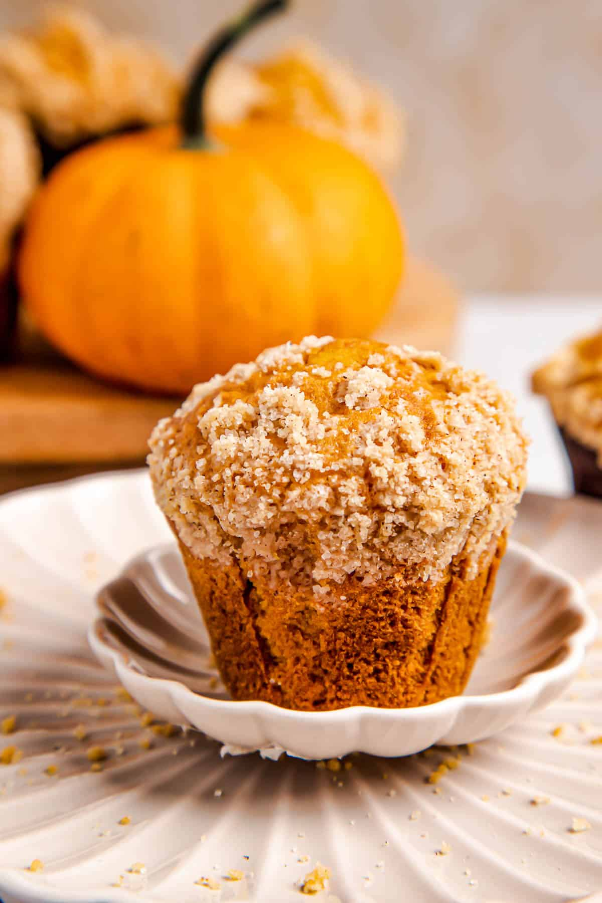 one pumpkin muffin on a white plate with three muffins behind it.